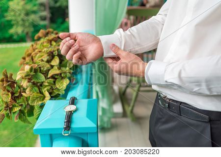 Man Buttons Cuff Link On Cuffs Sleeves Luxury White Shirt. Close Up Of Man Hand Wears White Shirt An