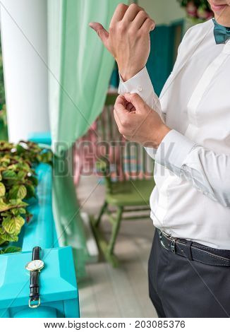 Man Buttoning Cuff On Luxury White Shirt Sleeves. Close Up Of Man Hand Wears White Shirt And Cufflin