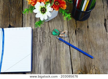 Top View Of  Pencils Case , Blue Pencil ,opened Notebook  And Green Pencil Sharpener On Wood Table W