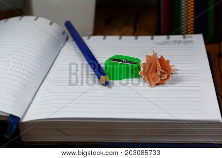 Pencils Case , Blue Pencil ,opened Notebook  And Green Pencil Sharpener On Wood Table