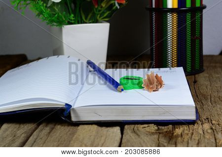 pencils case blue pencil opened notebook and green pencil sharpener on wood table with flowers in vase