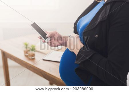Unrecognizable pregnant woman holding smartphone with blank screen. Cropped image of expectant businesswoman using mobile phone and touching her belly