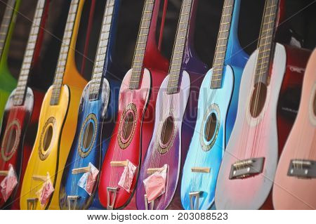 A Hanging Assortment of Shiny Colorful Miniature Guitars