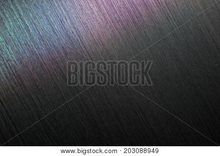 Brushed metal or hairline metal in dim light.  With rainbow sheen or reflection.