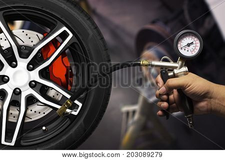 Hand holding an inflator gauge tools Alloy wheels of racing car and metal brake disc with red caliper Hand of mechanic man checking air pressure gauge of car tyre. Automotive parts concept.