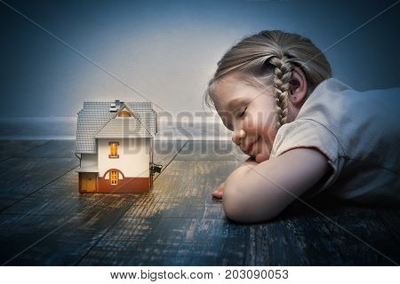 The little girl fell asleep on the floor in front of the magic fairy house