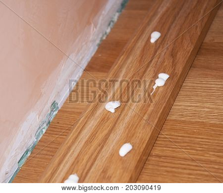Close up on Oak Wood Parquet Installation.Caulking silicone from cartridge glue on wooden batten. Oak floor repair.