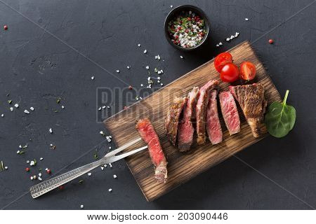 Rare rib eye steaks with herbs and spices on wooden board with meat fork and tomato at dark background with copy space, top view