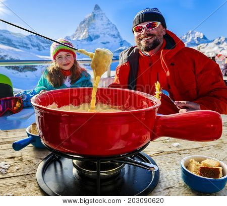 Swiss fondue dinner - family skiers enjoying break for lunch, mountain view Matterhorn, Switzerland.