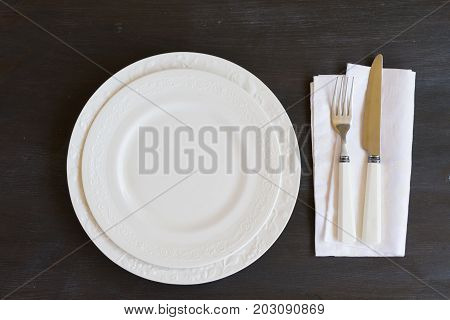 Tableware - set of plates and utencils on dark wooden table