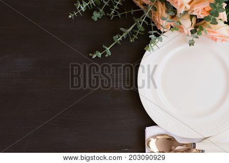 Tableware - set of plates and utencils on dark wooden table with copy space