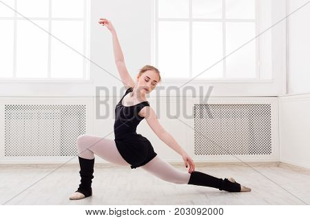 Beautiful graceful ballerina in black stretching in white class room background. Ballet class training, copy space