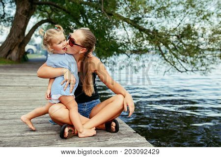 Group portrait of happy white Caucasian mother and daughter child having fun outside. Mom and child girl playing hugging kissing in park on pier by water lake. Candid authentic real lifestyle.