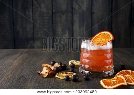 Cool alcohol cocktail at wooden background. Blood orange margarita with tequila on rustic table with citrons and chocolate snacks. Bar and restaurant backdrop with copy space for drinks menu