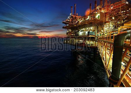 Offshore oil and rig platform in sunset or sunrise time. Construction of production process in the sea. Power energy of the world.