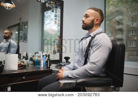 A successful, attractive, masculine lumberjack-style hipster man sitting and waiting in a chair on a blurred barbershop background. Professional hairdressing service center. Copy space.