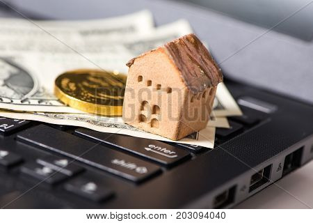 The cash and gold with the house model on laptop the business finance and technology concept