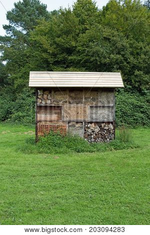 Insect hotel on a meadow, blue cloudless sky