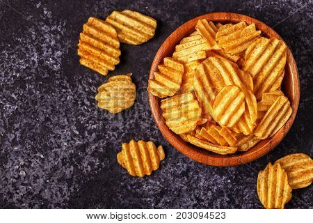 Crispy Potato Chips In A Bowl On Stone Background.