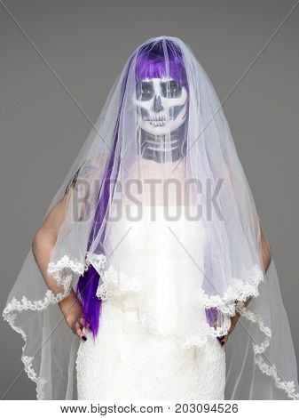 Portrait of woman looks at the camera with terrifying halloween skeleton makeup and purple wig bridal veil wedding dress over gray background. Black wedding
