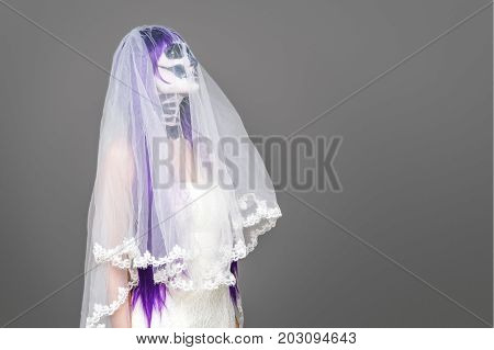 Portrait of woman looks upwards with terrifying halloween skeleton makeup and purple wig bridal veil wedding dress over gray background. Black wedding. Copy space