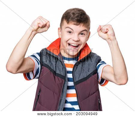 Cheerful handsome teen boy with raising hands. Emotional portrait of caucasian happy cute smiling male child, isolated on white background. Lucky child celebrating triumph.