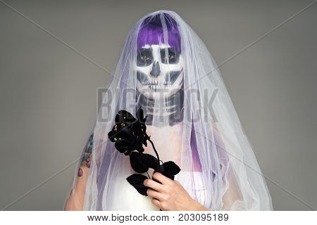 Portrait of woman with terrifying halloween skeleton makeup and purple wig bridal veil wedding dress holds a black rose in his hands over gray background. Black wedding