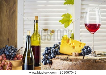 Still life of red wine with wooden keg. Wine bottle glass of red wine with cheese and grape on a old wooden barrel. Wine tasting and production concept.