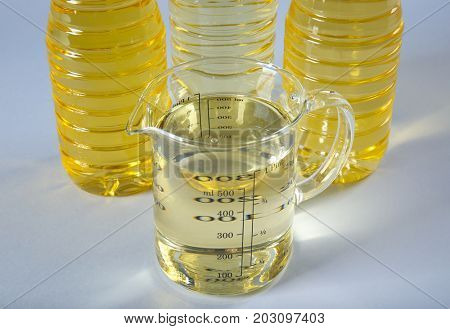 Beaker and bottles with cooking oil on light background