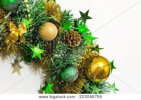Golden green shiny Christmas decoration of tinsel bows balls beads cones and stars.