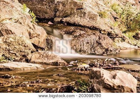 Water stream. Long time photo exposure. Detailed natural photo. Brook scene. Yellow photo filter.