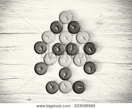 Symbolic christmas tree of tea lights on the wooden background. Black and white photo.