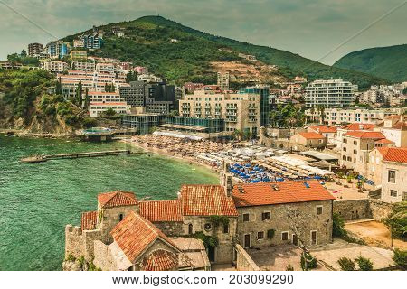 Budva, Montenegro - August 20, 2017: Fragment of the old town of Budva: ancient walls and a red tiled roof and a view of a modern beach, Montenegro, Europe. Budva is one of the best and most popular resorts of the Adriatic Riviera.