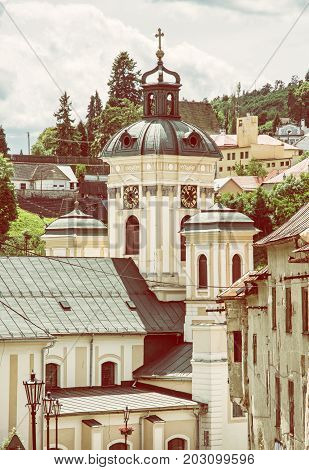 Church of the assumption Banska Stiavnica Slovak republic. Cultural heritage. Holy cross. Clock tower. Religious architecture. Yellow photo filter.