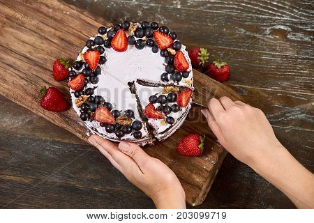 Closeup of Making Sponge Cake with Strawberry. Hand putting icing on freshly baked cake