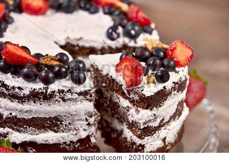 a cut of cake with whipped cream and strawberry fruits on wood table background