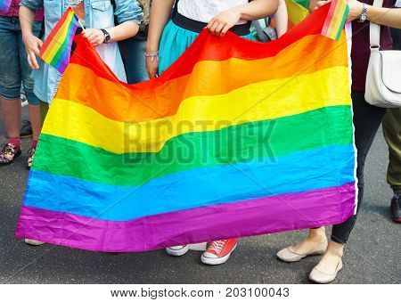 Concept of sexual minority. People holding gay rainbow flag outdoors