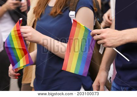 Concept of sexual minority. People holding gay rainbow flags outdoors
