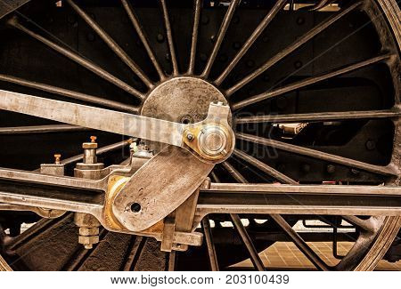 Detail of steam locomotive wheel. Old train scene. Yellow photo filter.