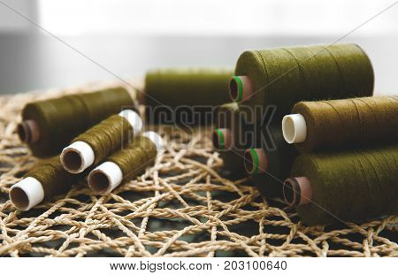 Spools of green threads on wicker mat