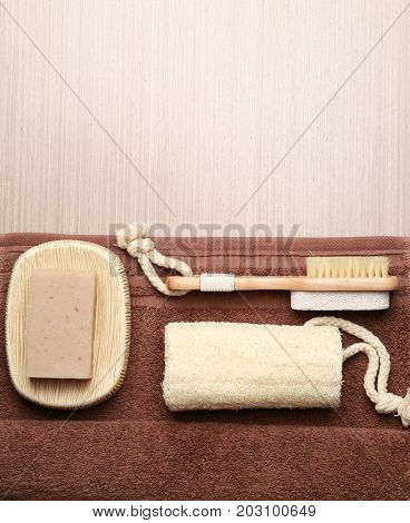 Bath accessories, towel and soap on wooden background