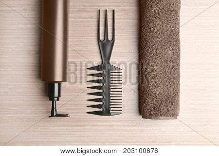 Lotion, comb and towel on wooden background