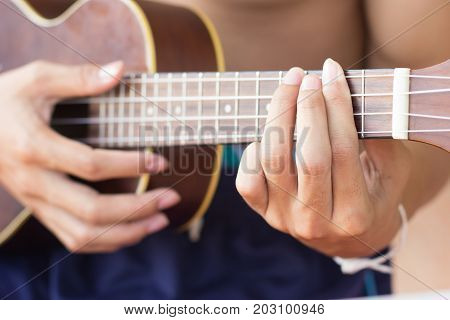 Close up playing ukulele touch chord string instrument body part