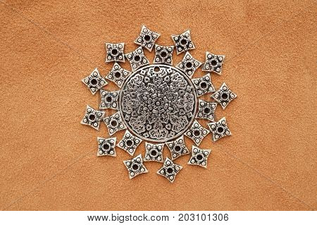 Sun or mandala made of metal medallion and findings on suede background
