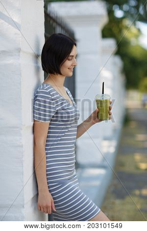 Gorgeous, positive, smiling relaxing woman leaning on a fence in a park on a blurred natural background. Healthy female drinking a vegetarian green smoothie. Stylish brunette woman in a trendy dress.