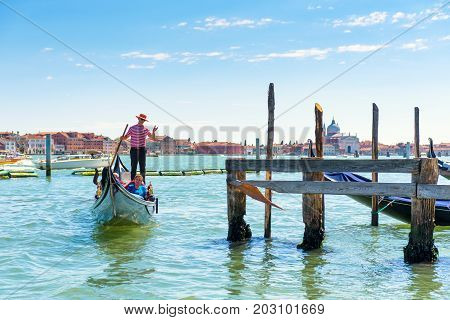 Venice, Italy - May 21, 2017: Gondolas with tourists floats along the Venetian lagoon near the pier. The gondola is the most attractive tourist transport in Venice.