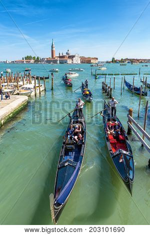 Venice, Italy - May 21, 2017: Gondolas with tourists are sailing into the canal from the Venetian lagoon. San Giorgio Maggiore in the background. The gondola is the most attractive tourist transport in Venice.
