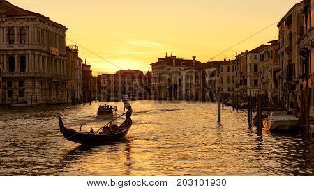 Grand Canal with gondola and motor boats at sunset in Venice, Italy. Grand Canal is one of the major water-traffic corridors and tourist attraction in Venice. 16:9 widescreen.