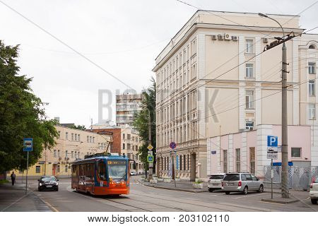 MOSCOW RUSSIA - JULY 17 2017: MIIT Humanitarian Institute (right) tram and cars in Obraztsova Street on summer day. Obraztsova Street is located in North-Eastern Administrative District of Moscow.