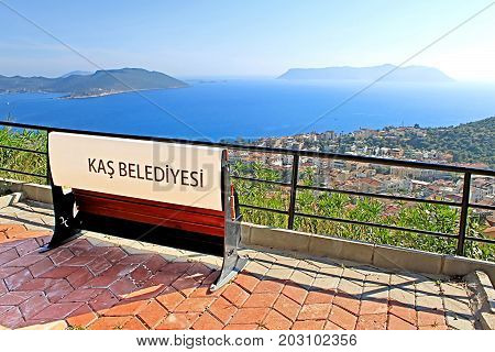 Bench and view of harbour of city Kas (Kash) in Turkey and Greek island Kastelorizo